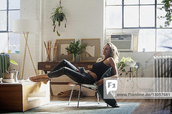 Glückliche Frau sitzt zu Hause auf einem Stuhl
