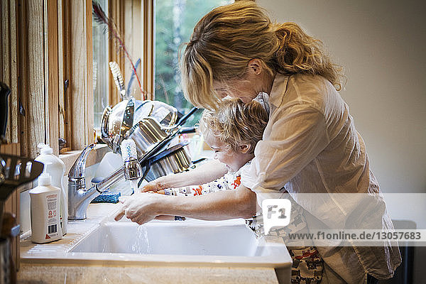 Mother assisting son in washing hands at kitchen sink