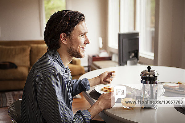 Side view of man having breakfast at home