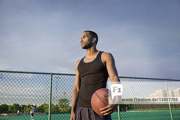 Thoughtful sportsman with basketball standing in court against sky