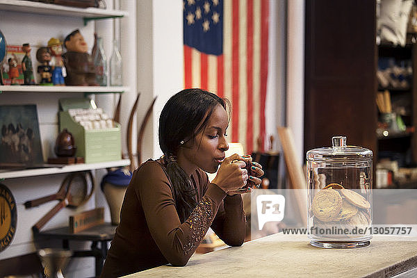 Woman drinking coffee while sitting at table in cafe
