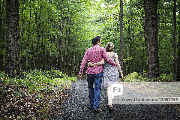 Rear view of couple with arms around walking on gravel road in forest