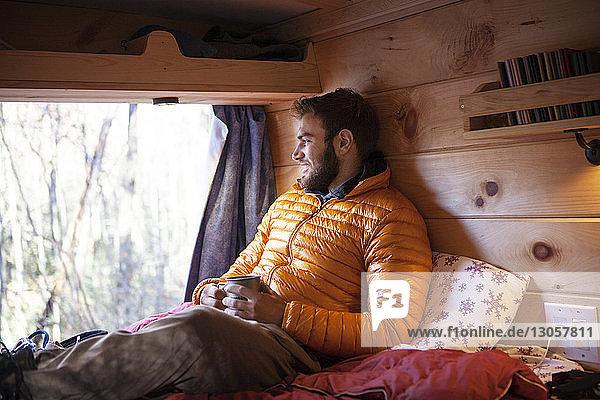 Lächelnder Mann mit Becher schaut weg  während er im Wohnmobil auf dem Bett sitzt