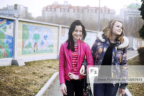 Fröhliche Freundinnen stehen mit Arm in Arm