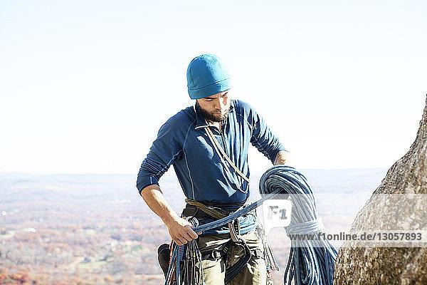 Mann bereitet sich auf Klettern vor  während er gegen den Himmel steht