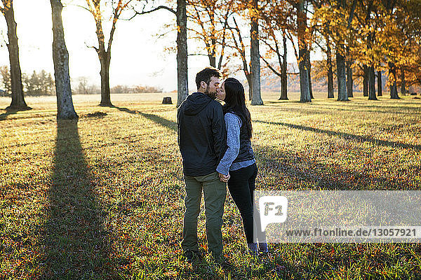 Couple kissing while standing on field