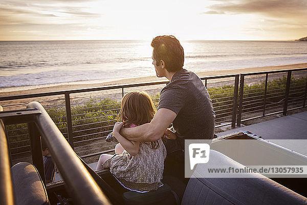 Vater und Tochter schauen auf die Aussicht  während sie bei Sonnenuntergang auf einem Pick-up sitzen