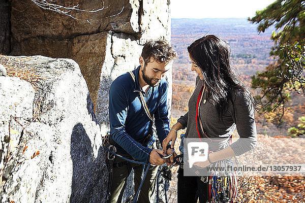 Mann hilft seiner Freundin beim Klettern