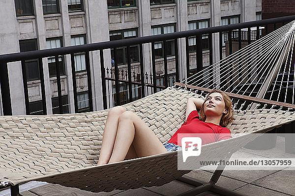 Woman relaxing on hammock in patio