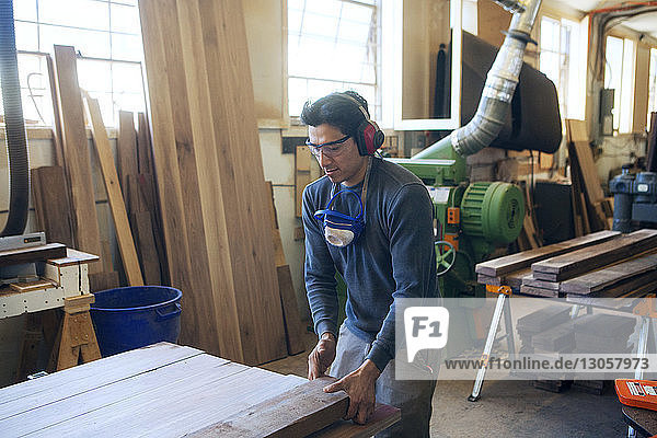 Male carpenter holding wooden plank at workshop