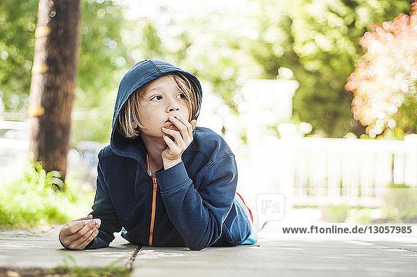 Boy holding chalk while lying on footpath
