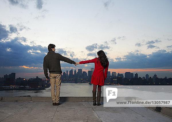 Rückansicht eines Paares  das in der Dämmerung Hand hält und sich gegen das Stadtbild stellt