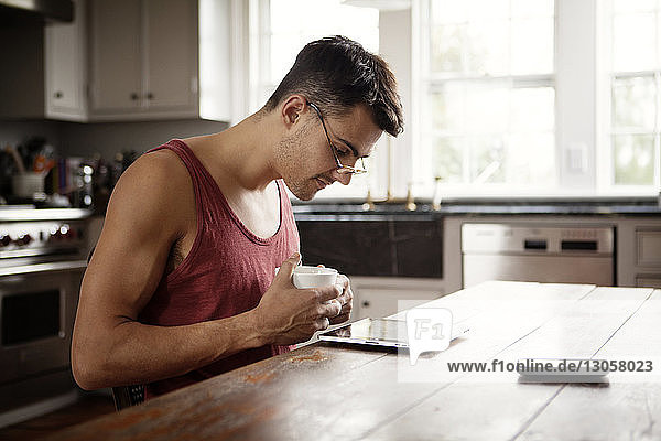 Man with coffee cup looking at tablet computer while sitting by table in kitchen
