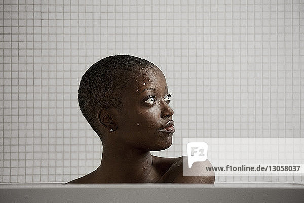 Thoughtful woman bathing in bathtub at home