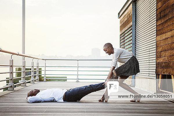 Playful woman pulling man's legs lying on floorboard at pier