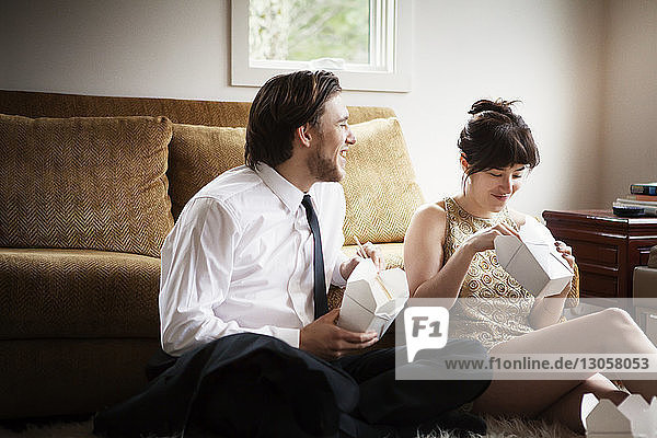 Cheerful couple sitting on rug at home