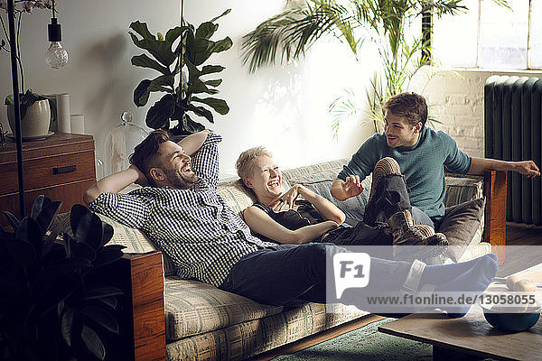 Glückliche Freunde unterhalten sich beim Entspannen auf dem Sofa zu Hause
