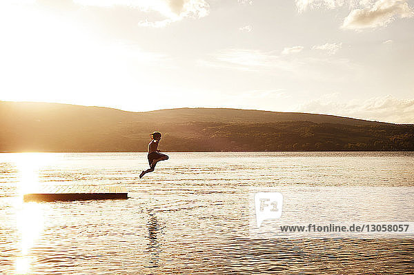 Boy diving into lake against sky during sunset