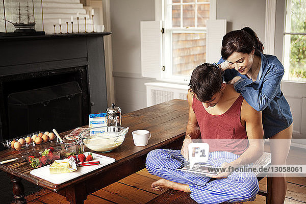 Couple searching recipe using tablet computer in kitchen at home
