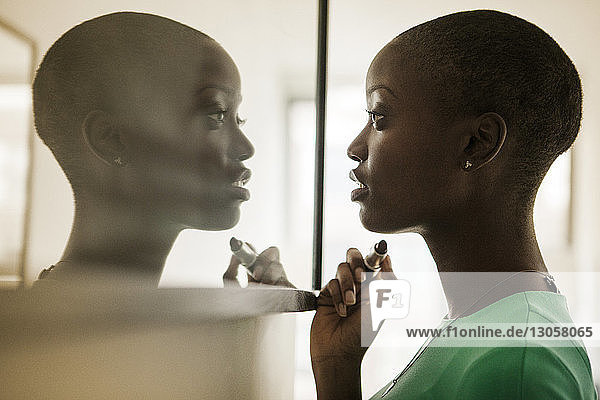 Woman looking at mirror while standing at home