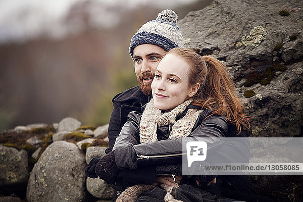 Couple looking away while leaning on rocks