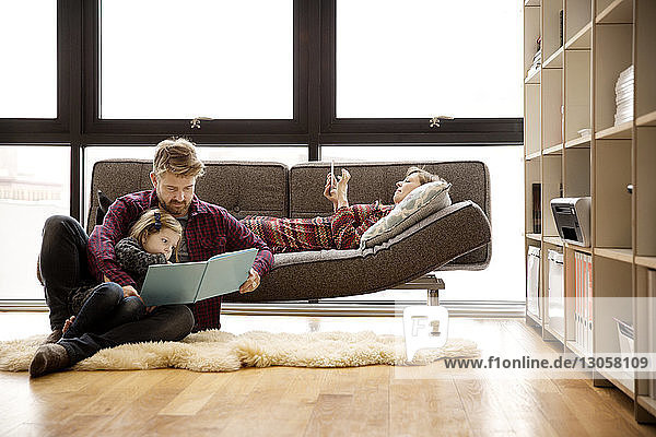 Father and daughter reading book by woman relaxing on sofa at home