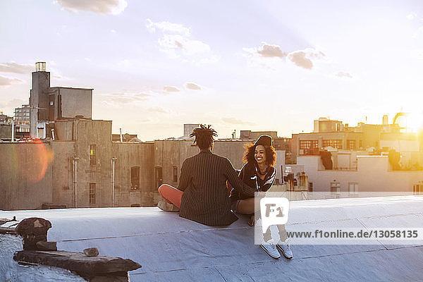 Glückliches Paar sitzt auf Stützmauer gegen Gebäude
