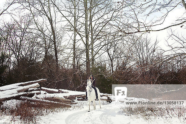 Frau zu Pferd auf Schneefeld sitzend