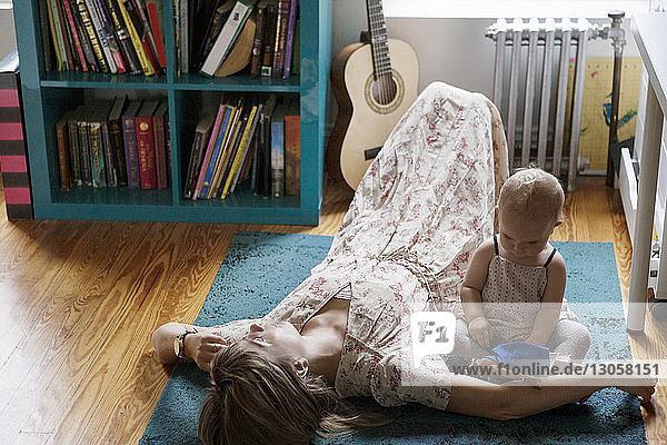 Hochwinkelansicht der Mutter  die schläft  während das Baby mit einem Spielzeug auf dem Teppich spielt