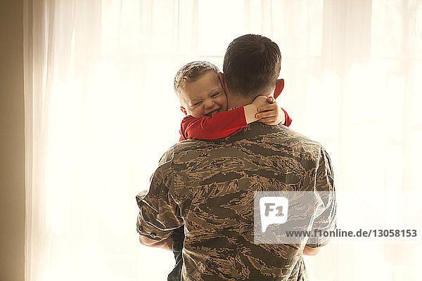 Rückansicht eines Vaters  der seinen Sohn zu Hause umarmt