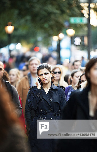 Woman talking on phone while walking in crowd