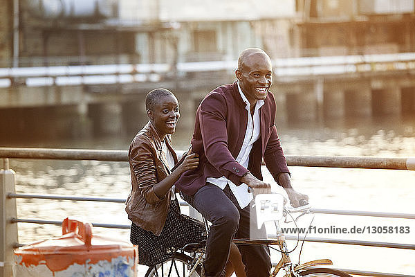 Happy couple cycling by railing against river