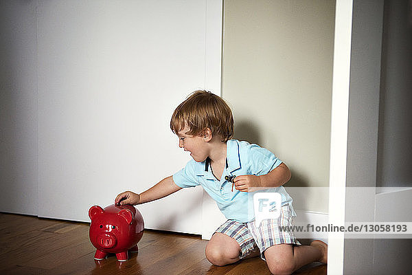 Boy adding coins to his piggy bank while sitting at home