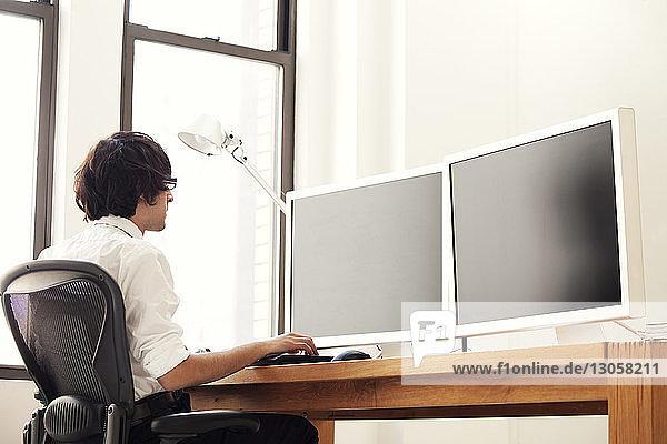 Mann benutzt Desktop-Computer  während er im Büro auf einem Stuhl sitzt