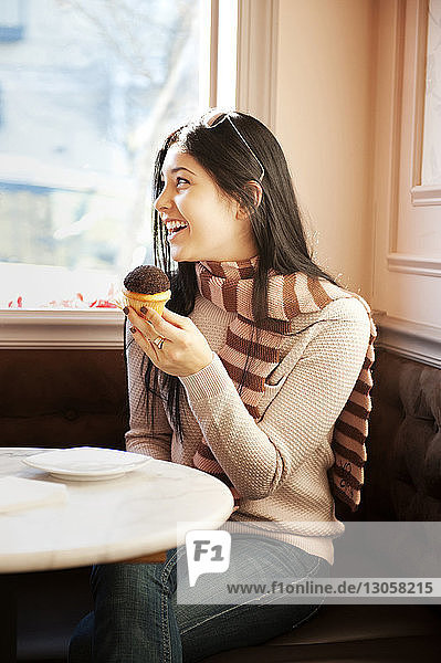 Glückliche Frau hält Muffin  während sie im Restaurant sitzt