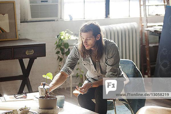 Mann bewässert Pflanze  während er zu Hause auf einem Stuhl sitzt