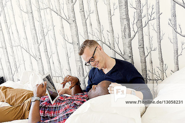 Man lying on boyfriend's lap while holding tablet computer on bed