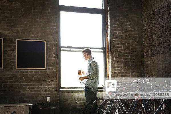 Mann mit Kaffeetasse steht zu Hause am Fenster