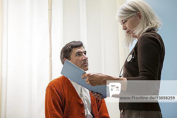 Patient schaut sich im Krankenhaus die Akte des Arztes an