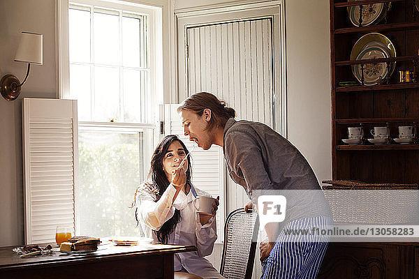 Frau füttert ihren Freund  während sie zu Hause am Fenster sitzt