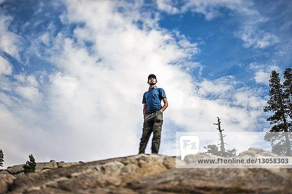 Tiefwinkelansicht eines jungen Mannes auf einer Felsformation gegen den Himmel