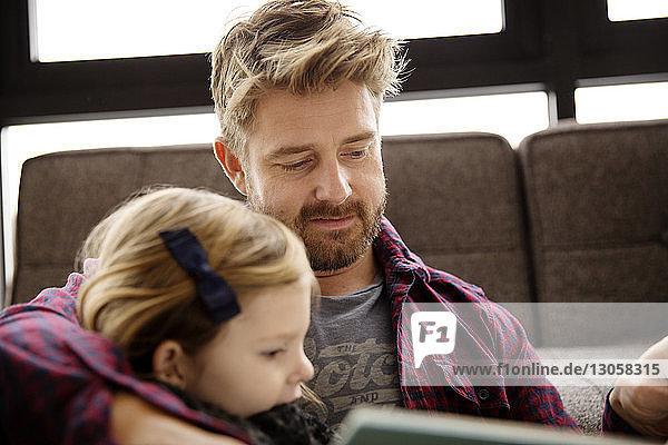 Vater und Tochter lesen Buch im Wohnzimmer