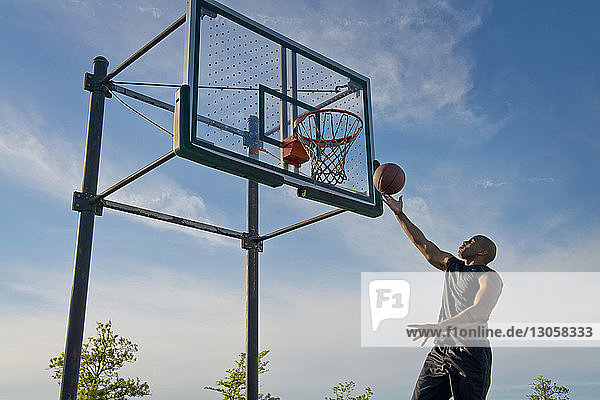 Low angle view of sportsman dunking ball in hoop --against sky