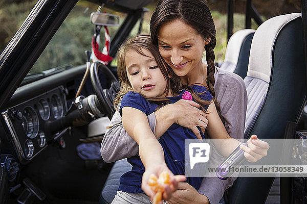 Glückliche Mutter hält Mädchen mit Orange im Pickup