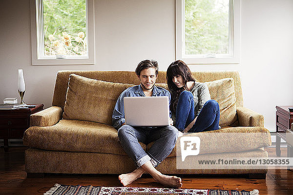 Man using laptop computer while sitting with girlfriend on sofa at home