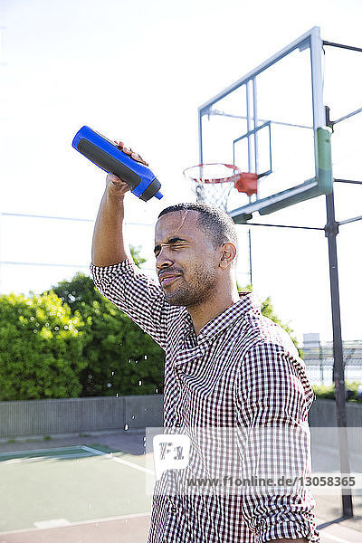 Man pouring water on head while standing in basketball court