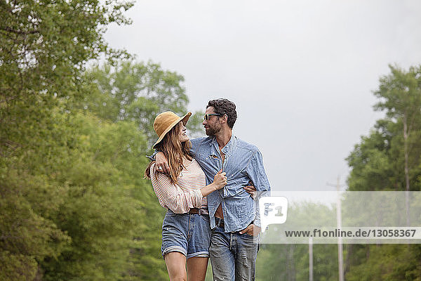 Couple taking while walking by trees against sky