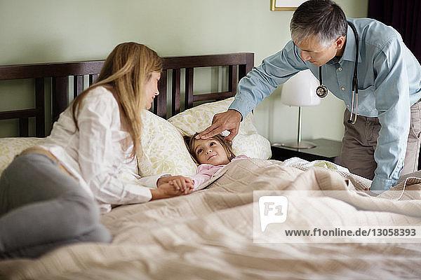 Arzt untersucht Mädchen im Bett mit Mutter