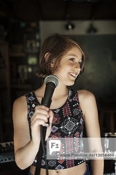 Girl looking away while singing in recording studio