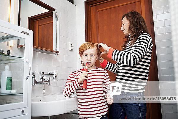Junge putzt Zähne  während die Mutter im Badezimmer die Haare kämmt